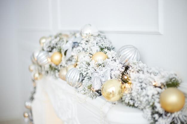 Стильный новогодний интерьер в гостиной с елкой, белым камином, подарками и украшениями. празднование рождества.
