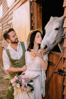 Stylish newlyweds hugging near horse, country style