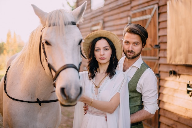 Stylish newlyweds stand near horse and look into camera