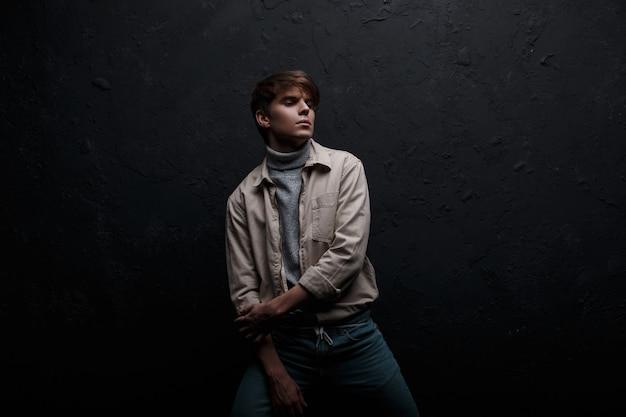 スタイリッシュで素敵な魅力的な若い男は、黒い壁の近くで屋内でポーズをとるスタイリッシュなヴィンテージブルージーンズの灰色のセーターのファッショナブルなジャケットでファッショナブルな髪型をしています。アメリカの現代人モデル