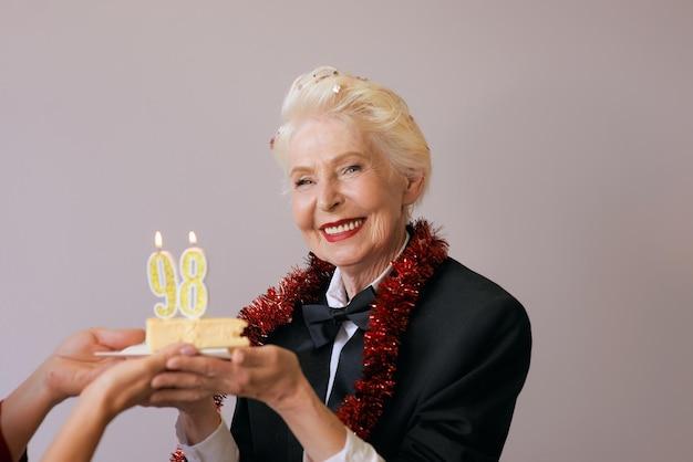 ケーキで彼女の誕生日を祝う黒いスーツを着たスタイリッシュな98歳の女性