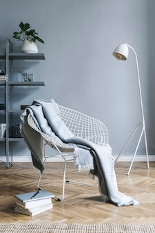 Stylish nordic living room with design armchair, coffee table, white lamp, bookstand, furniture, carpet, plant and elegant accessories in modern home decor