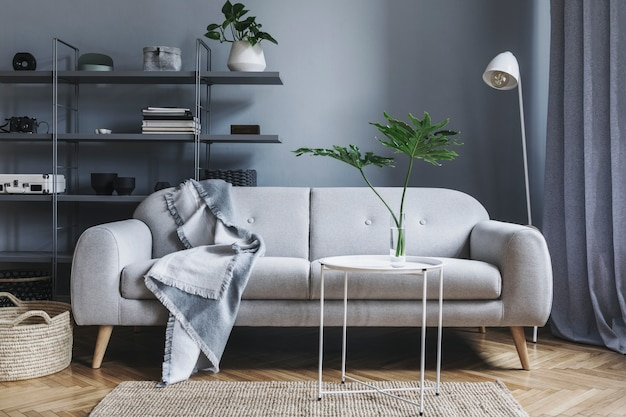 Stylish nordic living room with design grey sofa, coffee table, white lamp, bookstand, furniture, carpet, plant and elegant accessories in modern home decor