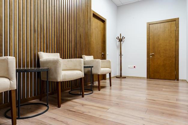 안락 의자와 커피 테이블이있는 세련된 사무실 대기실