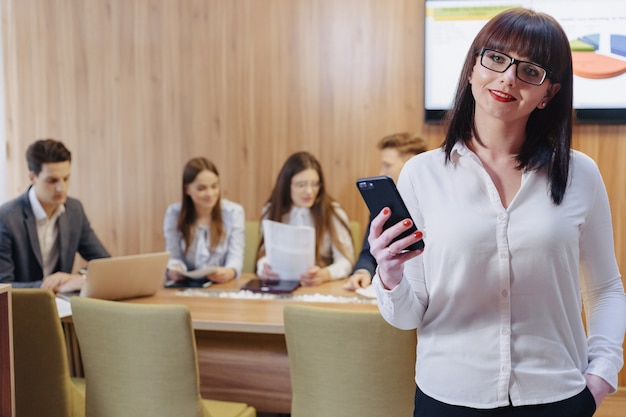 Stylish office worker woman in glasses with phone in hands against background of working colleagues