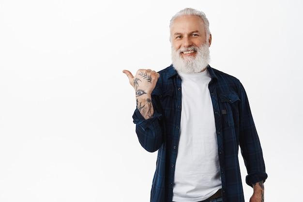Elegante vecchio, anziano hipster con barba e tatuaggi che punta il dito a sinistra, mostrando promo da parte, dimostrando pubblicità su spazio bianco copia, parete dello studio