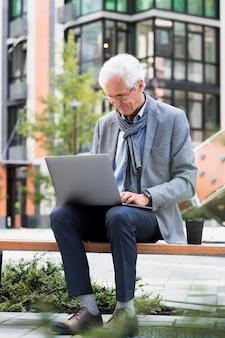 Elegante uomo anziano in città che usa il laptop