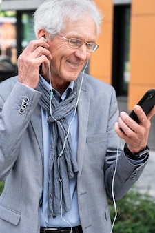 Stylish older man in the city using smartphone and earphones for video call
