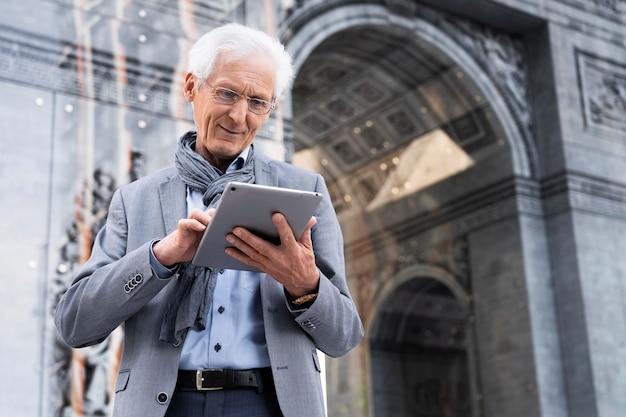 Elegante uomo anziano in città che utilizza tablet