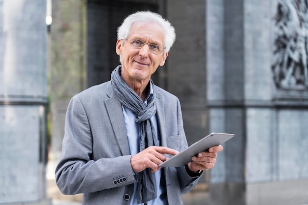 Stylish older man in the city using tablet