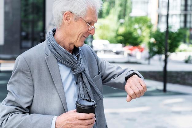 スマートウォッチを見ている街のスタイリッシュな老人
