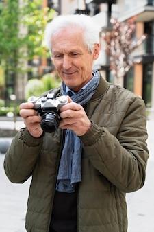 Стильный пожилой мужчина в городе снимает фото на камеру
