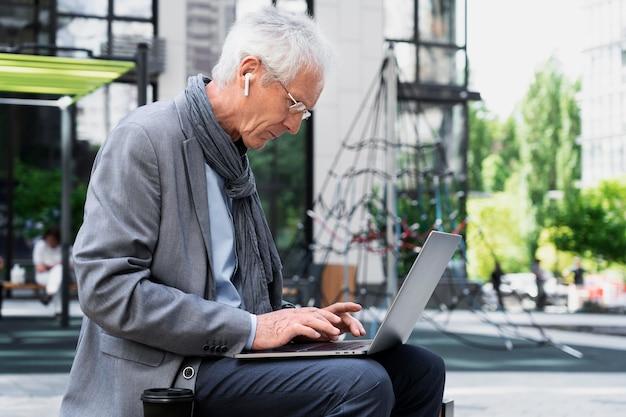 ラップトップを使用して街のスタイリッシュな老人