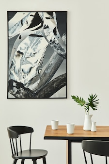 나무 패밀리 테이블, 검은 색 의자, 커피 컵, 꽃병에 열대 잎, 벽의 추상적 인 고통과 우아한 액세서리가있는 세련된 열린 공간 인테리어. 현대 가정 장식.