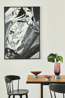 나무 테이블, 검은 색 의자, deisgn 유리 트레이, 꽃병에 열대 잎, 벽의 추상적 인 고통과 우아한 액세서리가있는 세련된 열린 공간 인테리어. 현대 가정 장식 ..