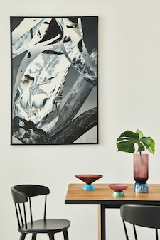 Stylish open space interior with wooden table, black chairs, deisgn glassy tray, tropical leaf in vase, abstract painitings on the wall and elegant accessories. modern home decor..