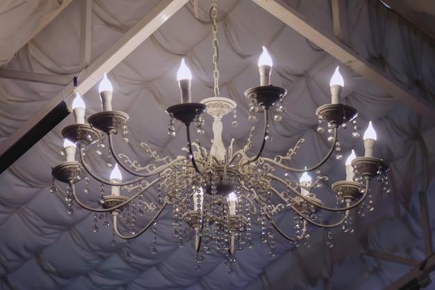 結婚式のテントの白い材料で作られたスタイリッシュな透かし彫りのシャンデリア。豪華な照明装飾のクローズアップ。サイトの著作権スペース