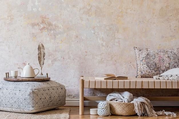 Стильный восточный интерьер гостиной с бежевым шезлонгом, декором из ротанга, большим пуфом с деревянным подносом и чайником, книгой и элегантными личными аксессуарами. концепция ваби-саби. скопируйте пространство. шаблон