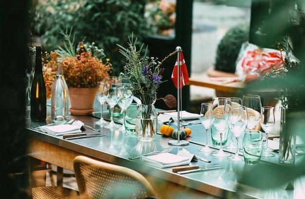 スタイリッシュな屋外ディナーパーティー。美しい野生の花の花束で飾られたテーブル