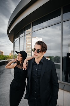 黒い服とメガネの若者のスタイリッシュなペアは、夕日のオフィスビルに立ち向かいます。