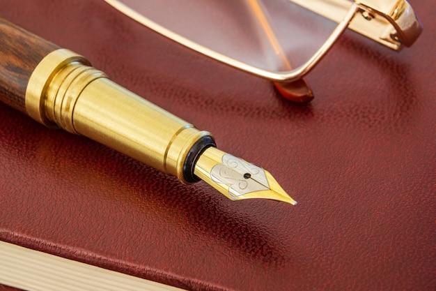 ゴールドメッキのペンと茶色のメモ帳のメガネでスタイリッシュなペン
