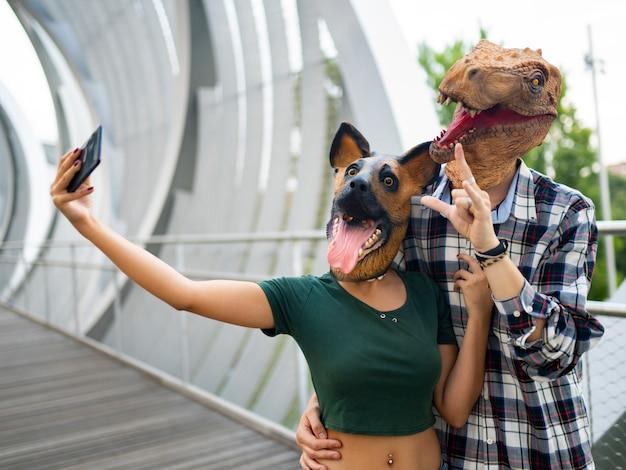 Стильные люди модная пара в маске тираннозавра и собаки