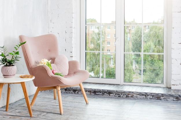 明るいミニマリストのインテリアにハート型の枕を備えたスタイリッシュなピンクのアームチェア