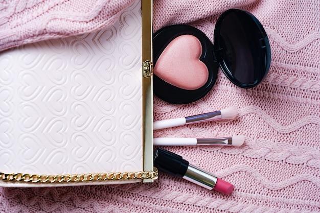 ピンクの背景にメイクアップアクセサリーの口紅の赤面ブラシとスタイリッシュなピンクのハンドバッグ