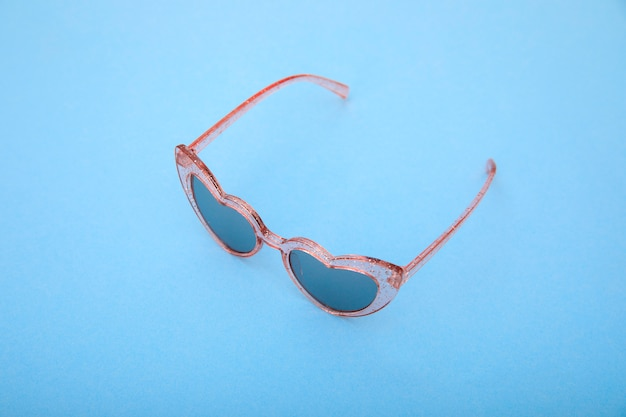 Stylish pink sunglasses on pastel blue. minimal summer concept.