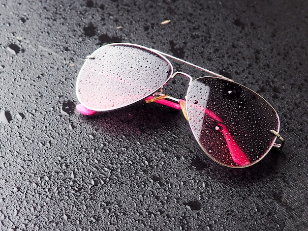 Stylish pink sunglasses with drops of water