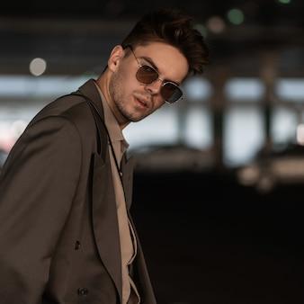 スタイリッシュな肖像画は、駐車場にブレザーとシャツを着たファッショナブルな外観の服を着た眼鏡をかけたハンサムな青年実業家の男
