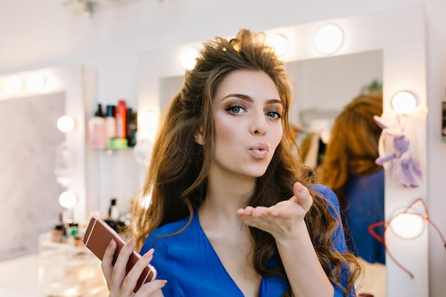 Stylish portrait attractive joyful model with beautiful coiffure sending a kiss to camera in hairdresser salon