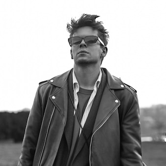 Stylish portrait cool young hipster man in fashionable dark sunglasses in vintage leather black jacket with trendy hairstyle outdoors. handsome guy fashion model posing on nature.black and white photo