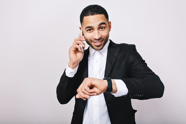 Stylish portrait elegant young man in white shirt and black jacket talking on phone, showing watch and smiling. businessman, work, meeting, cheerful mood, smiling