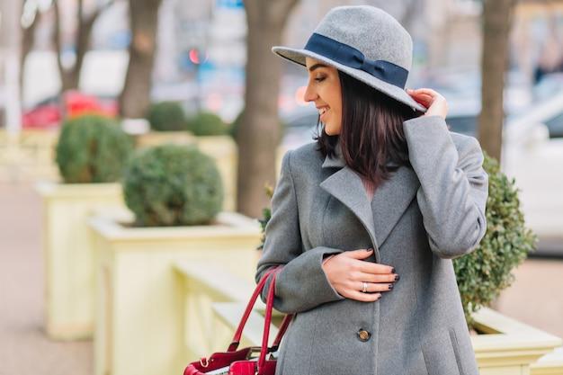 灰色のコートと帽子が街の通りにバッグと歩いて帽子でブルネットの髪を持つスタイリッシュな肖像画エレガントな若い女性。高級服、ファッショナブルな女性、側に笑顔。