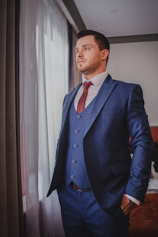 The stylish portrait of the groom preparing for the wedding ceremony in the morning. morning of the groom. morning preparation of the groom.