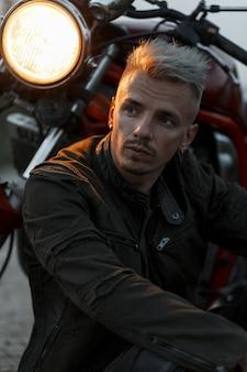 유행 군사 재킷에 잔인한 힙 스터 모델 남자의 세련된 초상화는 저녁에 빛으로 오토바이 근처에 앉아