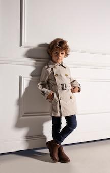Стильный портрет симпатичного кудрявого ребенка, позирующего спереди в дождевике