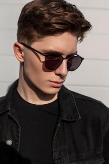 유행 검은 청바지에 헤어 스타일을 가진 세련된 초상화 도시 젊은이는 유행 선글라스에 착용