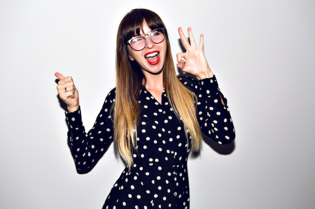 Stylish portrait of young hipster woman posing at white background, long ombre hairs, bright make up and clear sunglasses, vintage relevant dress.
