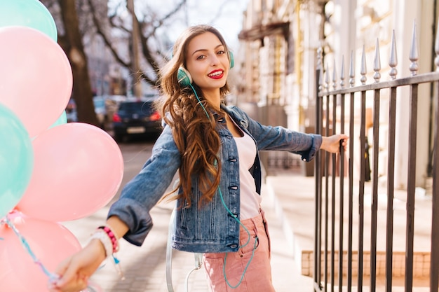 Elegante ragazza positiva che cammina per strada con un mazzo di palloncini colorati e si aggrappa alla recinzione in ferro.