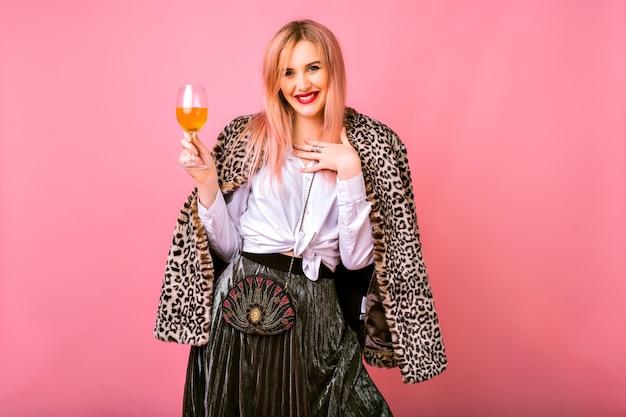 Elegante bella giovane donna positiva che si diverte, indossa un abito da cocktail scintillante da sera e un cappotto alla moda con stampa leopardata di pelliccia, sfondo rosa, godendosi la festa delle vacanze invernali.