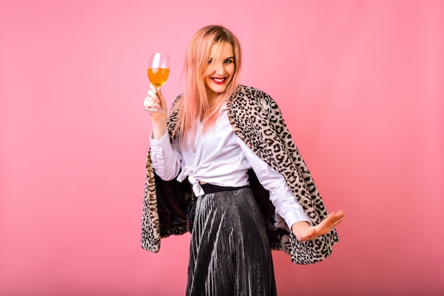Stylish positive pretty young woman having fun, wearing evening sparkling cocktail outfit and fur leopard printed trendy coat, pink background, enjoying winter holidays party.