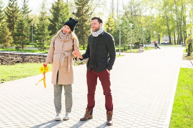 スタイリッシュな妊娠の概念-都市公園を歩いている流行の服を着た流行に敏感な夫と妻のカップルの肖像画。