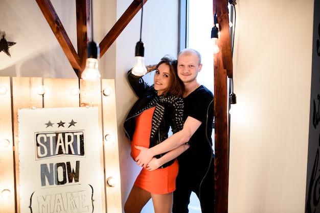 Стильная беременная пара в кожаной одежде и красном платье.