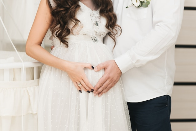 Stylish pregnant girl in white clothes and next to her husband hugs her stomach and keeps her hands in the shape of a heart