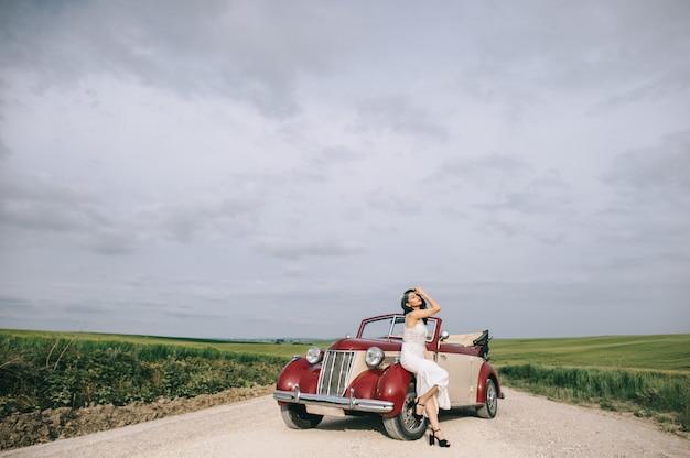 Стильная красивая невеста сидит на красной ретро-машине на полевой дороге