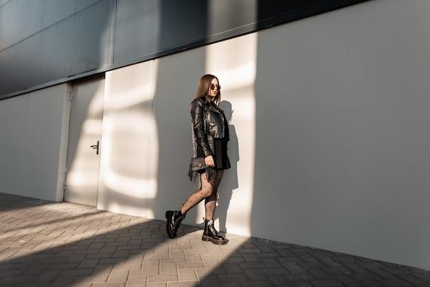 가죽 재킷, 드레스, 섹시한 스타킹, 부츠가 있는 검은색 세련된 옷을 입은 빈티지 선글라스를 착용한 세련되고 멋진 소녀 모델은 햇빛 아래 도시를 걷습니다.