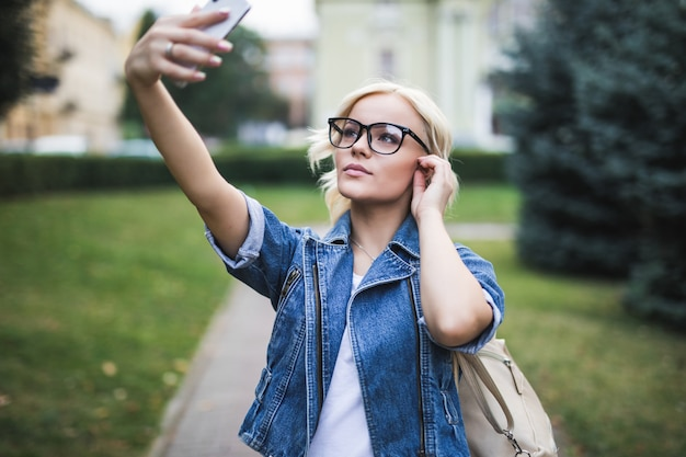 Стильная красивая модная блондинка в джинсовом люксе делает селфи на своем телефоне в городе утром