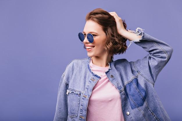 Ragazza graziosa alla moda in occhiali da sole che tocca i suoi capelli ondulati corti con il sorriso. meravigliosa donna caucasica ridendo.